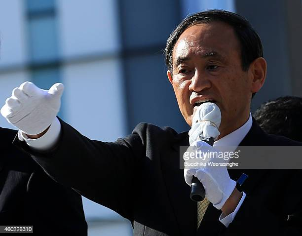 Japan's ruling Liberal Democratic Party Chief Cabinet Secretary Yoshihide Suga speaks to voters from the roof of a campaign bus during his party...
