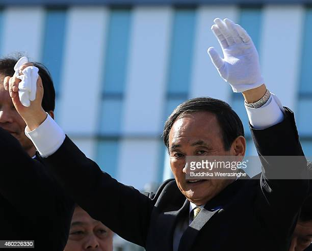 Japan's ruling Liberal Democratic Party Chief Cabinet Secretary Yoshihide Suga waves to voters from the roof of a campaign bus during his party...