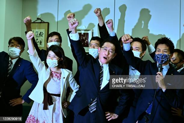 Japan's ruling Liberal Democratic Party Policy Research Council's chairman Fumio Kishida raises his fist in the air with his faction members after...