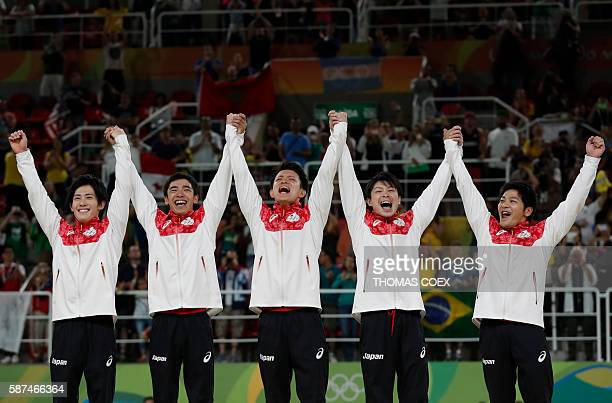 Japan's Ryohei Kato Japan's Kenzo Shirai Japan's Yusuke Tanaka Japan's Kohei Uchimura and Japan's Koji Yamamuro celebrate on the podium after winning...