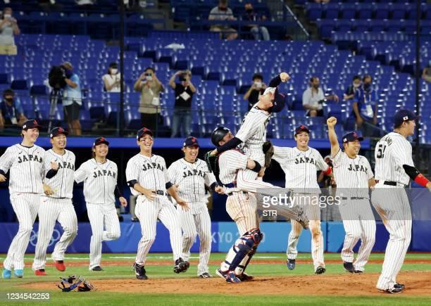 Japan's Ryoji Kuribayashi celebrates with catcher Takuya Kai after their victory during the Tokyo 2020 Olympic Games baseball gold medal game between...