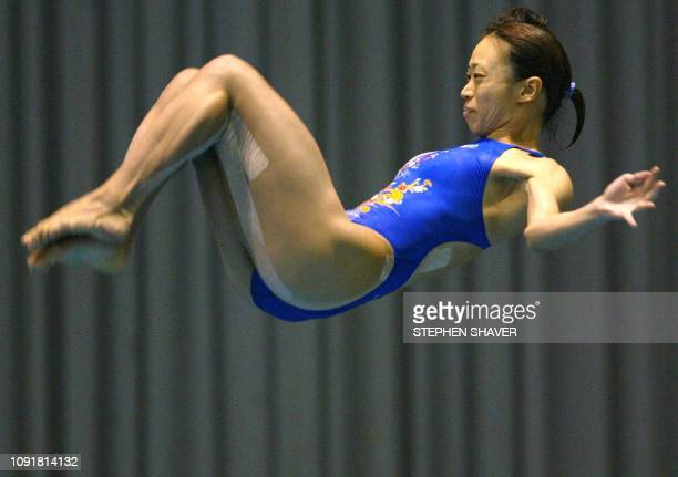 Japan's Ryoko Nishi breaks from a somersault during the women's 3metre springboard final 10 October 2002 at the 14th Asian Games in Busan China's Guo...
