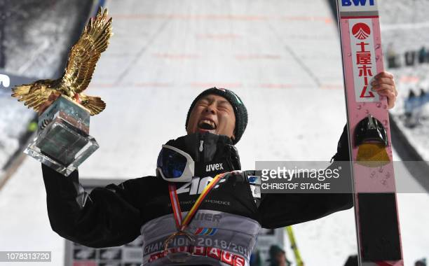 Japan's Ryoyu Kobayashi celebrates with the overall trophy after the winner ceremony of the fourth stage of the FourHills Ski Jumping tournament in...