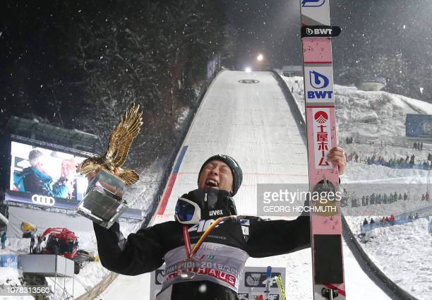 TOPSHOT Japan's Ryoyu Kobayashi celebrates with the trophy after winning the fourth stage of the FourHills Ski Jumping tournament in Bischofshofen...