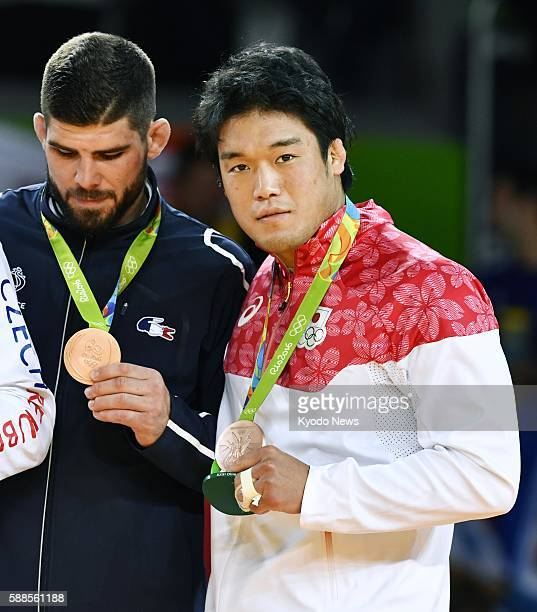 Japan's Ryunosuke Haga and France's Cyrille Maret attend a medal ceremony after both won bronze medals in the men's judo 100kilogram category at the...