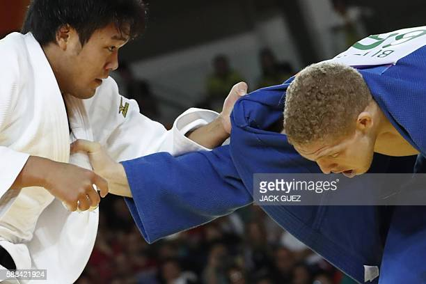 Japan's Ryunosuke Haga competes with Brazil's Rafael Buzacarini during their men's 100kg judo contest match of the Rio 2016 Olympic Games in Rio de...