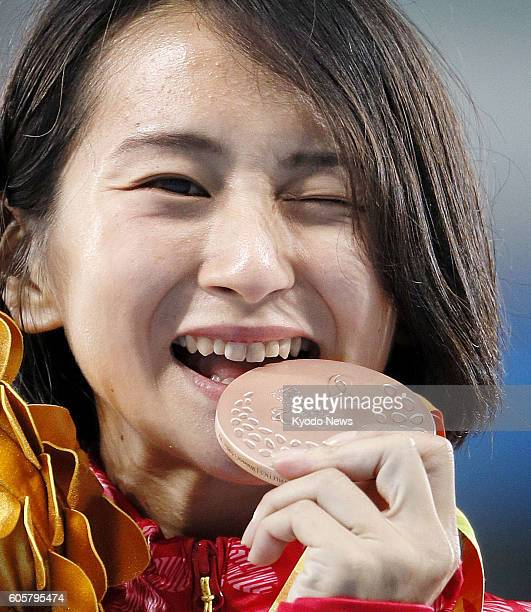 Japan's Sae Tsuji celebrates with the bronze medal she won in the women's 400meter T4547 class for athletes with single or double full or partial arm...