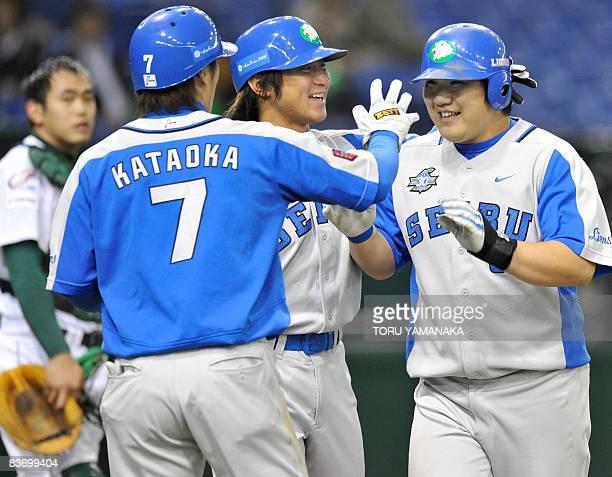 Japan's Saitama Seibu Lions slugger Takeya Nakamura is congratulated by his teammate Yasuyuki Kataoka and Hiroshi Hirao beside China's Tianjin Lions...