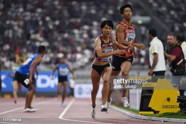 Japan's Saki Takashima receives the baton from Tomoya Tamura in the Mixed 4 x 400m Relay heats at the 2019 IAAF World Athletics Championships at the...