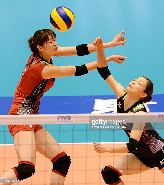 Japan's Saori Kimura and libero Arisa Sato receive the ball during their FIVB volleyball women's Grand Champions Cup match against Thailand in Tokyo...