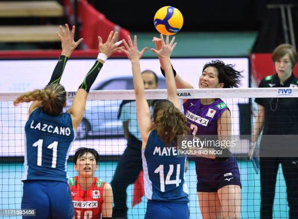 Japan's Sarina Koga spikes the ball over Argentina's Julieta Lazcano and Victoria Mayer during the FIVB Women's World Cup volleyball match between...