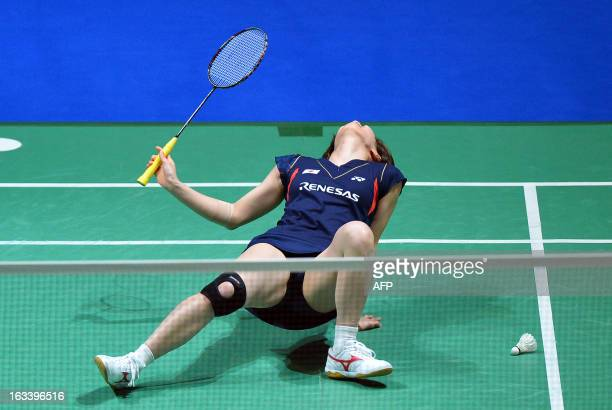 Japan's Satoko Suetsun falls to the ground during the All England Open Badminton Championships women's doubles semifinal match against China's Wang...