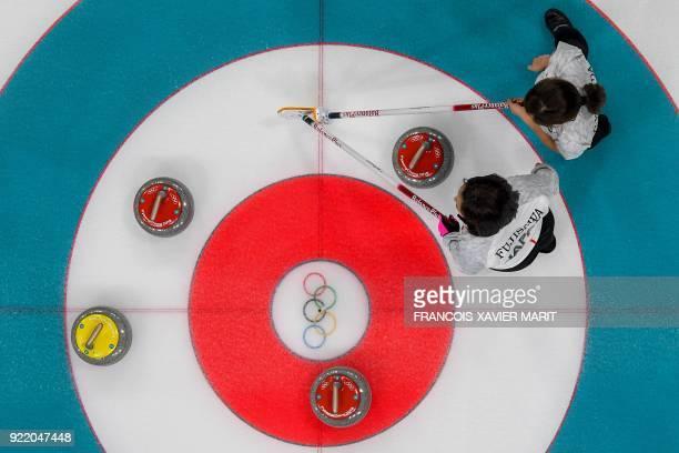 Japan's Satsuki Fujisawa and Japan's Yurika Yoshida look on at the stones during the curling women's round robin session between Switzerland and...