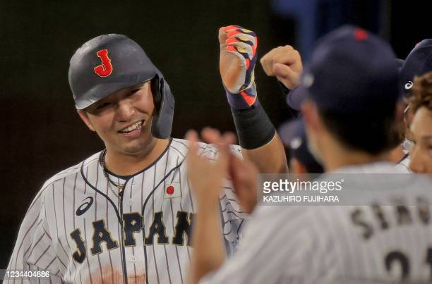Japan's Seiya Suzuki is celebrated his score by teammates making it 6-6 during the ninth inning of the Tokyo 2020 Olympic Games baseball round 2 game...