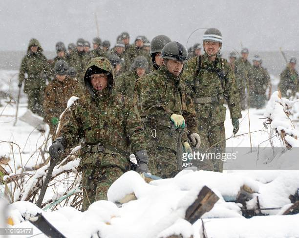 Japan's Self Defence Force soldiers search for missing people in a snow covered field in Miyako in Iwate prefecture on March 16 2011 Japan's Emperor...