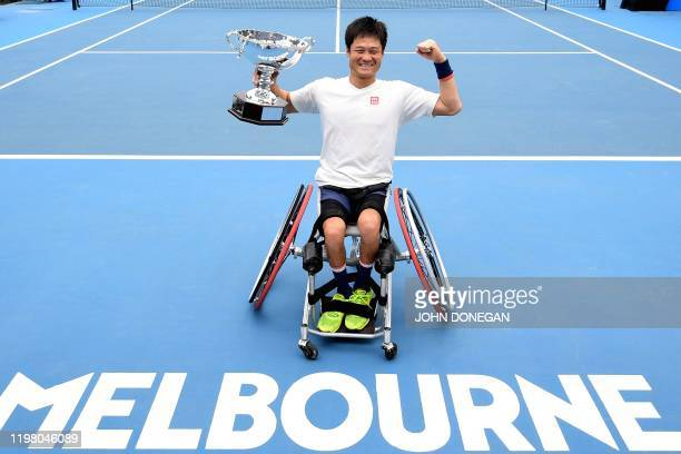Japan's Shingo Kunieda celebrates the winning trophy after beating Britain's Gordon Reid during their men's wheelchair singles match on day fourteen...