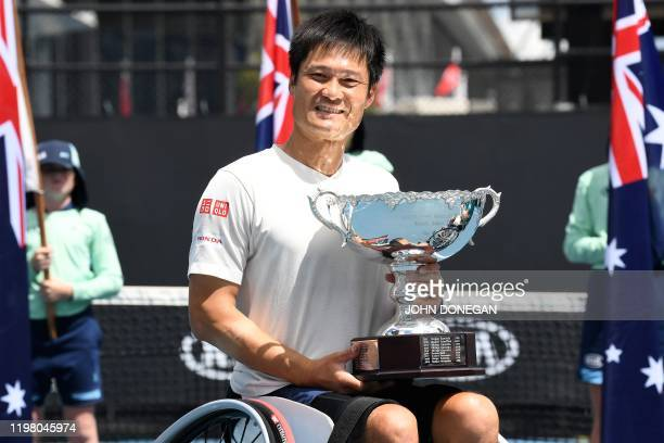 Japan's Shingo Kunieda celebrates with the winning trophy after beating Britain's Gordon Reid during their men's wheelchair singles match on day...