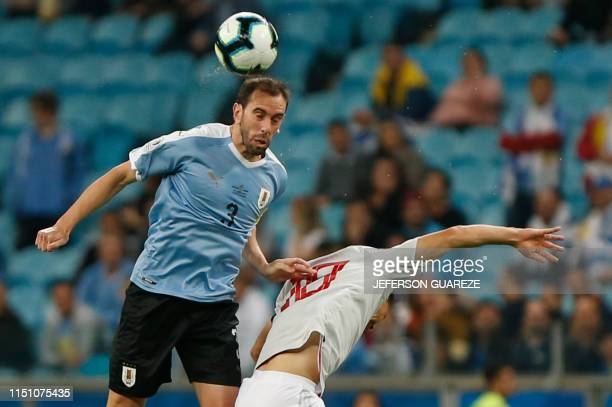 Japan's Shinji Okazaki and Uruguay's Diego Godin go for a header during the Copa America football tournament Group C match between Uruguay and Japan...