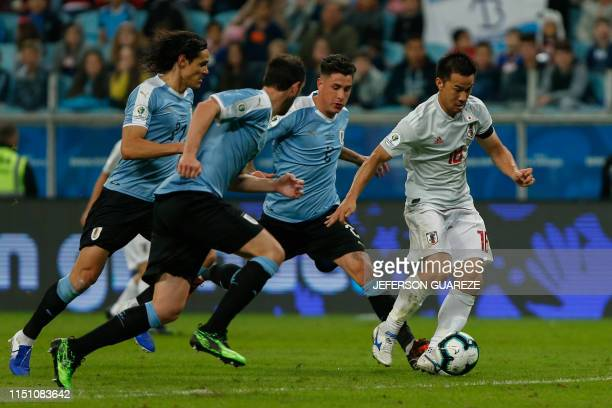 Japan's Shinji Okazaki is challenged by Uruguay's Jose Maria Gimenez during the Copa America football tournament Group C match between Uruguay and...