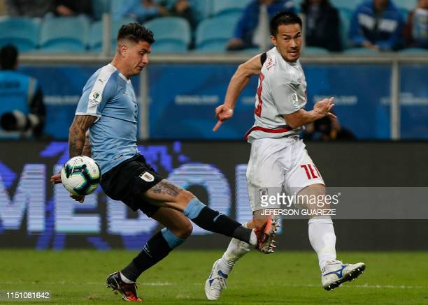 Japan's Shinji Okazaki kicks the ball as Uruguay's Jose Maria Gimenez tries to block during the Copa America football tournament Group C match...