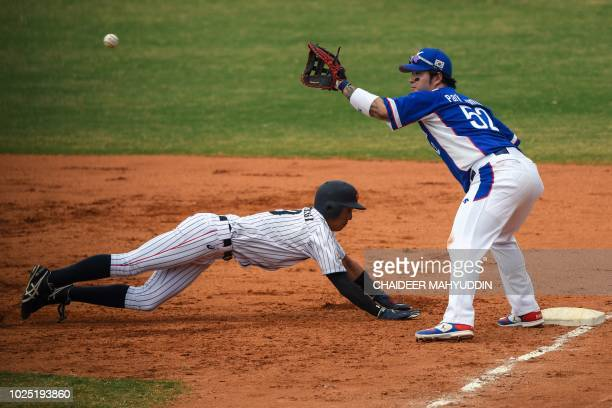 Japan's Sho Aoyagi dives back to first base on a pickoff attempt in front of South Korea's Park Byungho during the baseball men's super round match...