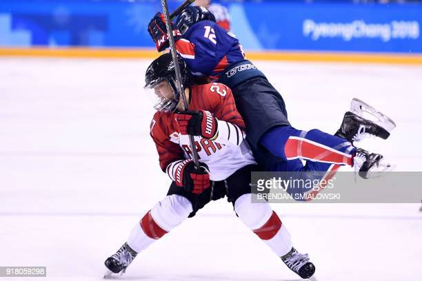 TOPSHOT Japan's Shoko Ono and Unified Korea's Kim Heewon collide in the women's preliminary round ice hockey match between Japan and the Unified...