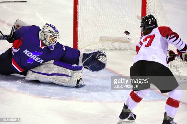Japan's Shoko Ono scores past Unified Korea's Shin So Jung in the women's preliminary round ice hockey match between Japan and the Unified Korean...