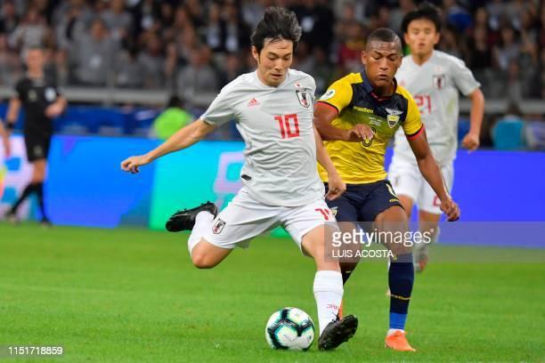 Japan's Shoya Nakajima strikes the ball to score against Ecuador during their Copa America football tournament group match at the Mineirao Stadium in...