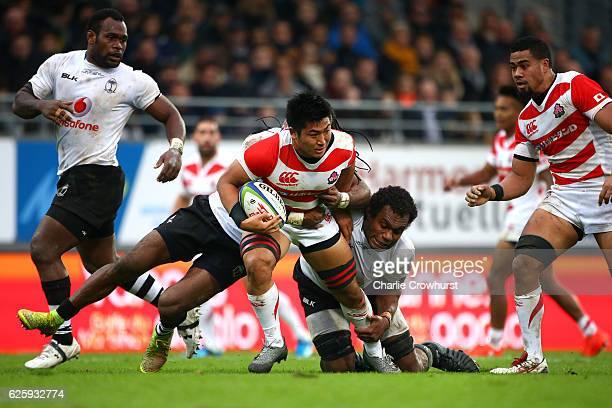 Japan's Shuhei Matsuhashi is tackled Fiji's Leone Nakarawa and Albert Vulivuli during the International match between Japan and Fiji at Stade de la...