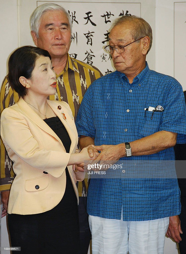 Japan's Social Democratic Party leader Mizuho Fukushima (L) is greeted by Okinawa Governor Hirokazu Nakaima (R) prior to their meeting at the Okinawa government office, on May 25, 2010. Fukushima, who has threatened to leave the ruling coalition over the contentious issue, visited the southern island and demanded that the unpopular base be moved off Okinawa instead.