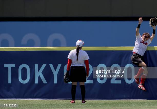 Japan's softball player Yamato Fujita smiles while joking with her teammate during their Tokyo 2020 Olympic Games softball training session at the...