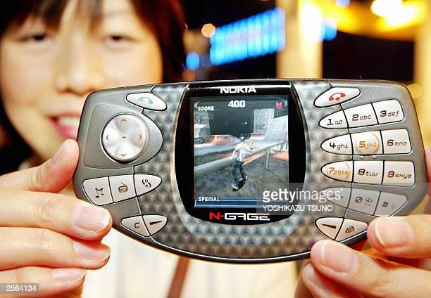 Japan's software house Gmode employee Izumi Hashimoto displays the Finish mobile communication giant Nokia's latest portable video game machine NGAGE...