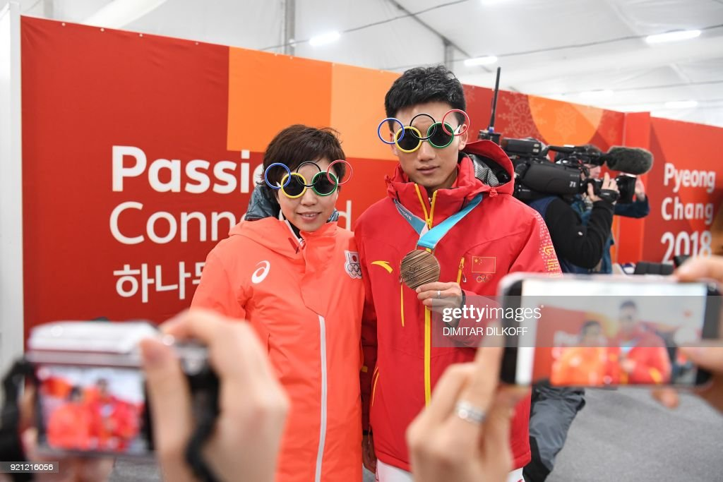Japan's speed skating gold medallist Nao Kodaira poses for a picture with China's speed skating bronze medallist Gao Tingyu backstage at the Athletes' Lounge during the medal ceremonies at the Pyeongchang Medals Plaza during the Pyeongchang 2018 Winter Olympic Games in Pyeongchang on February 20, 2018. / AFP PHOTO / Dimitar DILKOFF