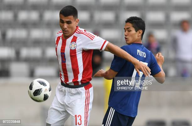 Japan's striker Yoshinori Muto and Paraguay's Junior Alonso vie for the ball during the international friendly football match between Japan and...