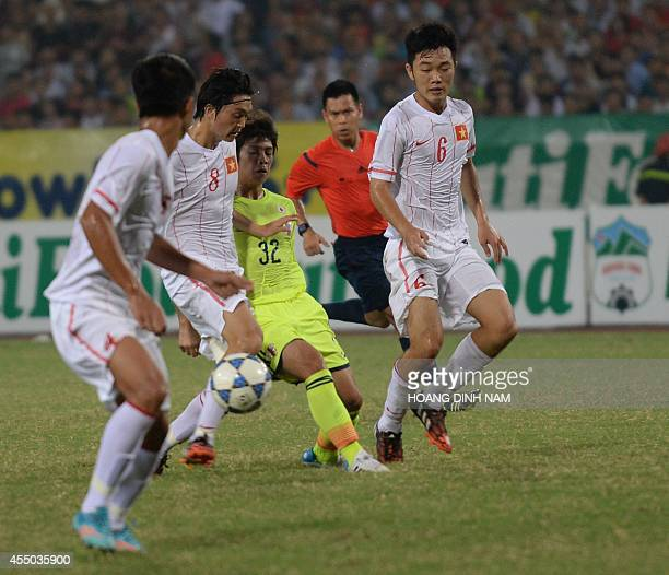 Japan's Sugimoto Taro fights for the ball with Vietnam's Nguyen Tuan Anh and Luong Xuan Truong during a match of the AFF Nutifood U19 Cup in Hanoi on...
