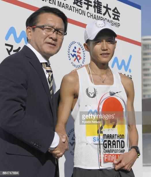 Japan's Suguru Osako shakes hands with Japan Association of Athletics Federation Development Project Leader Toshihiko Seko at Heiwadai Athletic...