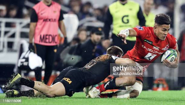 Japan's Sunwolves wing Hosea Saumaki is tackled by Argentina's Jaguares wing Sebastian Cancelliere during their Super Rugby match at Jose Amalfitani...