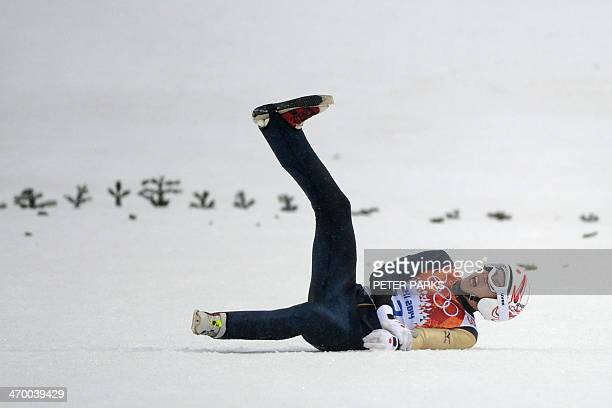 Japan's Taihei Kato clutches his arm after crashing during the Nordic Combined Individual LH / 10 km Ski Jumping competition at the RusSki Gorki...