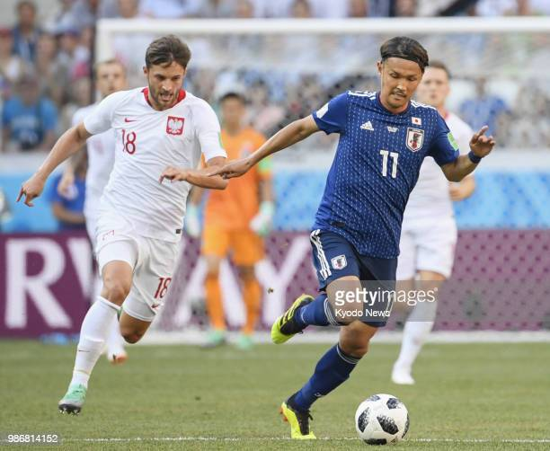 Japan's Takashi Usami dribbles the ball ahead of Poland's Bartosz Bereszynski during the first half of a World Cup group stage match at Volgograd...