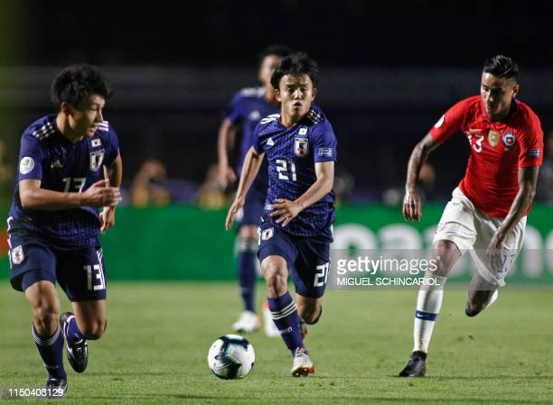 TOPSHOT Japan's Takefusa Kubo is chased by Chile's Erick Pulgar during a Copa America football tournament Group C match between Chile and Japan at...