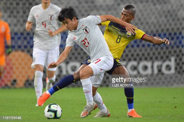 Japan's Takefusa Kubo vies for the ball with Ecuador's Carlos Gruezo during their Copa America football tournament group match at the Mineirao...