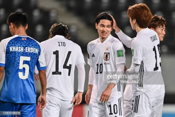 Japan's Takumi Minamino and Yuya Osako celebrate a goal during the FIFA World Cup Qatar 2022 Asian zone group F qualification football match between...
