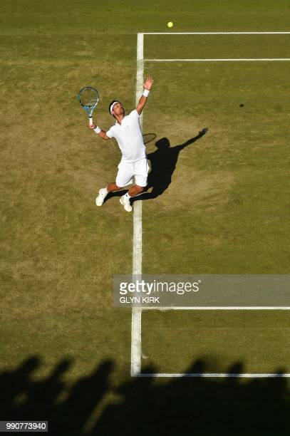 Japan's Taro Daniel serves against Italy's Fabio Fognini during their men's singles first round match on the second day of the 2018 Wimbledon...