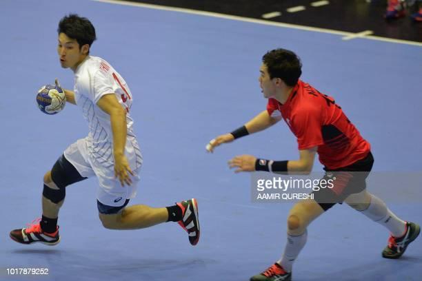 Japan's Tatsuki Yoshino controls the ball past South Korea's Na Seungdo during the men's handball preliminary Group B match between South Korea and...
