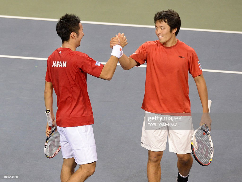 Japan's Tatsuma Ito (R) reacts with his partner Yasutaka Uchiyama (L) as they celebrate their victory against Indonesia's Christopher Rungkat and Elbert Sie in their men's doubles tennis match at t...