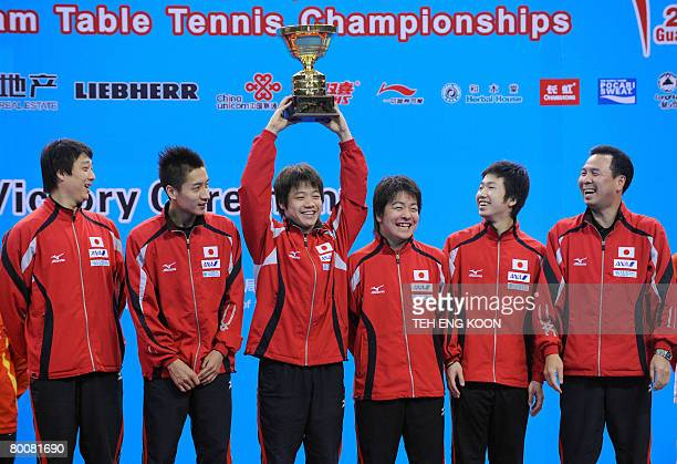 Japan's team members share a joke with their third runner up trophy on the podium of the World Team Table Tennis Championships in Guangzhou China's...