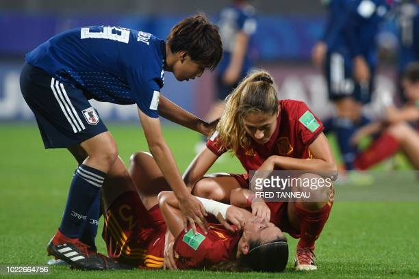Japan's team player comforts Spain's team players reacting at the end of the Women's U20 World Cup final football match between Spain and Japan on...