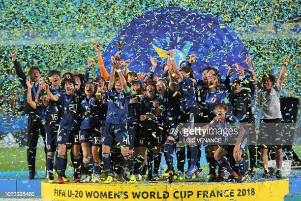 Japan's team players and members of staff celebrate with the trophy after winning the Women's U20 World Cup final football match between Spain and...