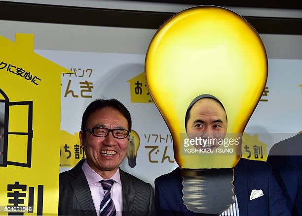 Japan's telecom giant Softbank president Ken Miyauchi smiles with comedian Tsukasa Saito wearing a mask of light bulb as he announces the company...