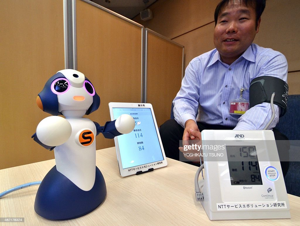 Japan's telecommunication giant NTT researcher demonstrates the desktop sized humanoid robot 'Sota' which was produced by Japanese robot company Vstone to control multiple electronic devices with NTT's cloud robotics technology in Tokyo on July 28, 2015. NTT started a field test to monitor elderly people at a retirement home in Tokyo and will develop various kind of services for elderly people and children with the robot. AFP PHOTO / Yoshikazu TSUNO